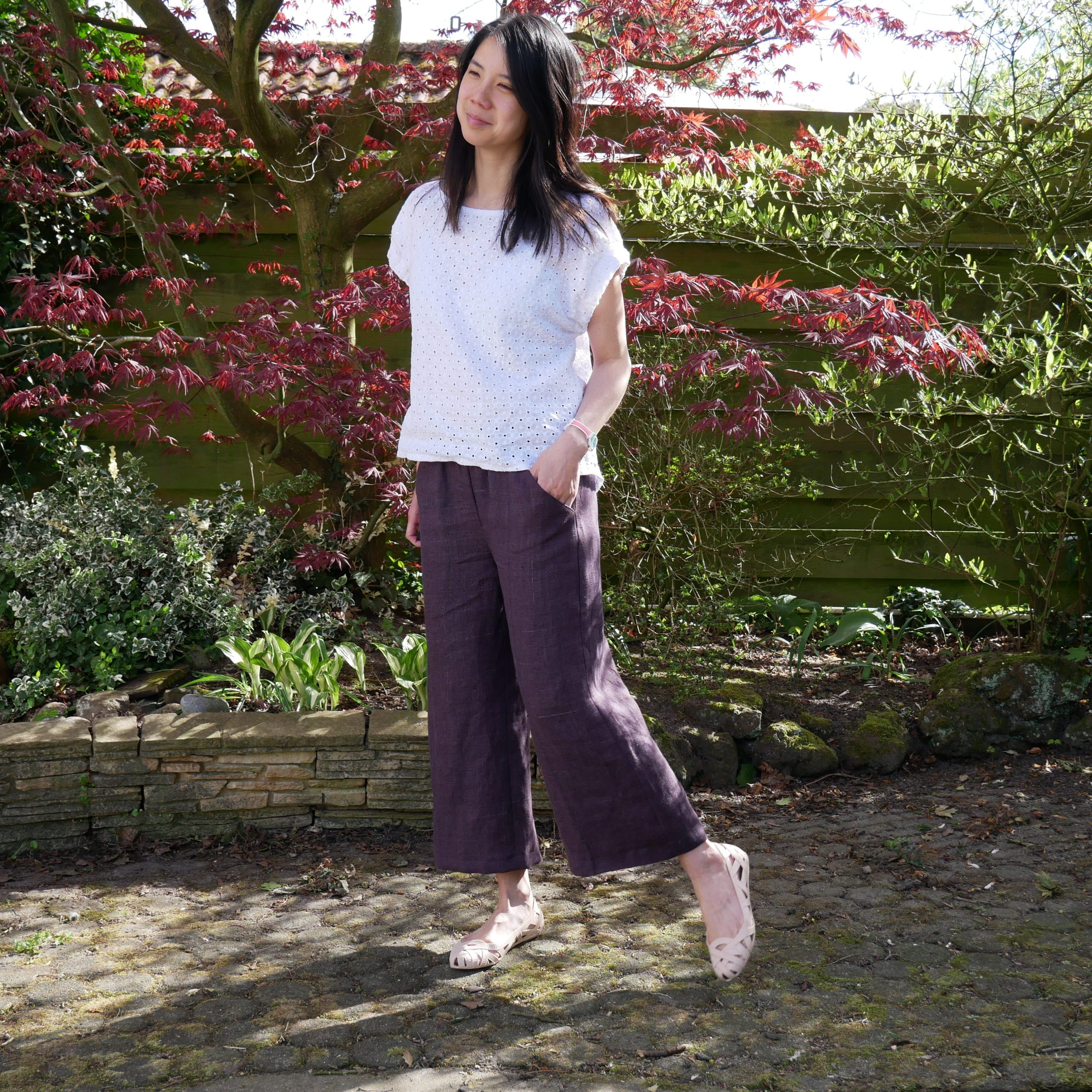 Kate wears a Fibre Mood Frances - white linen eyelet blouse - and Fibre Mood Benita - mulberry coloured linen pants