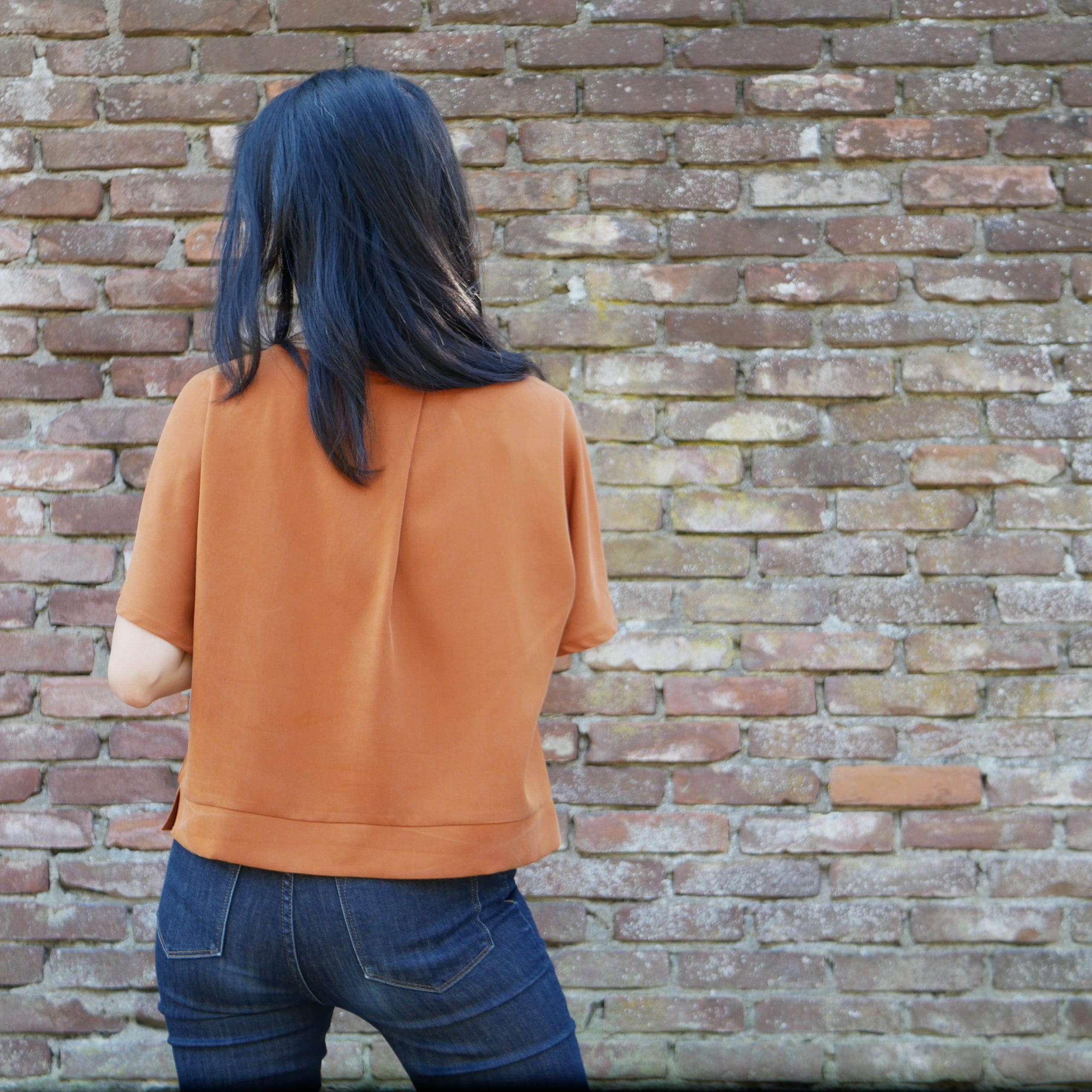 Kate wears a copper coloured top against a brick wall (back view)