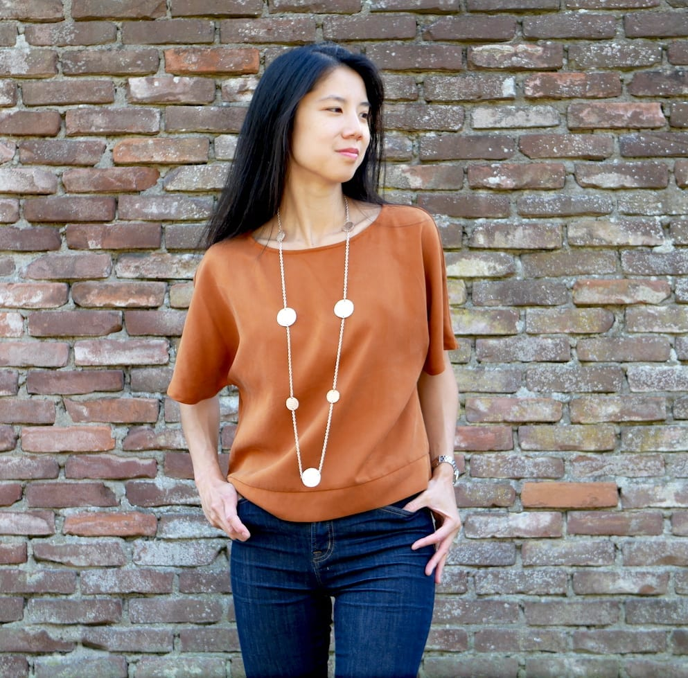 Kate wears a Fibre Mood Giulia, a copper coloured top against a brick wall (front view)