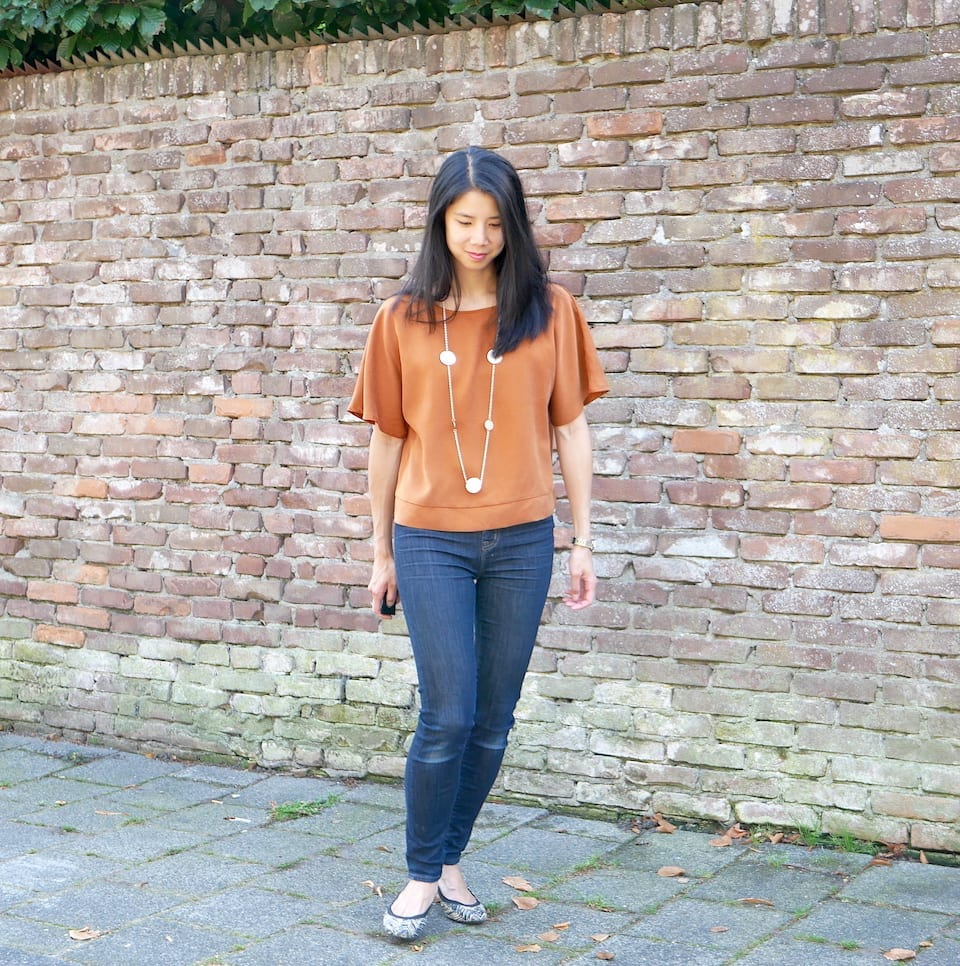 Kate wears a copper coloured top with dark denim jeans against a brick wall (front view)