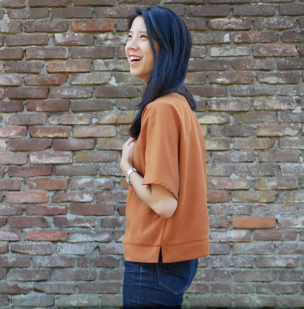 Kate wears a copper coloured top against a brick wall. There is a side split on the hem.