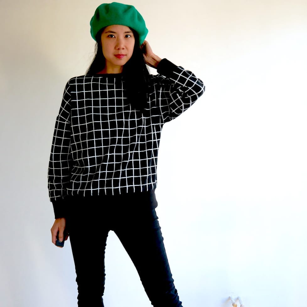 Just Patterns Tyra Tee sweater in black, worn with a green beret and black jeans