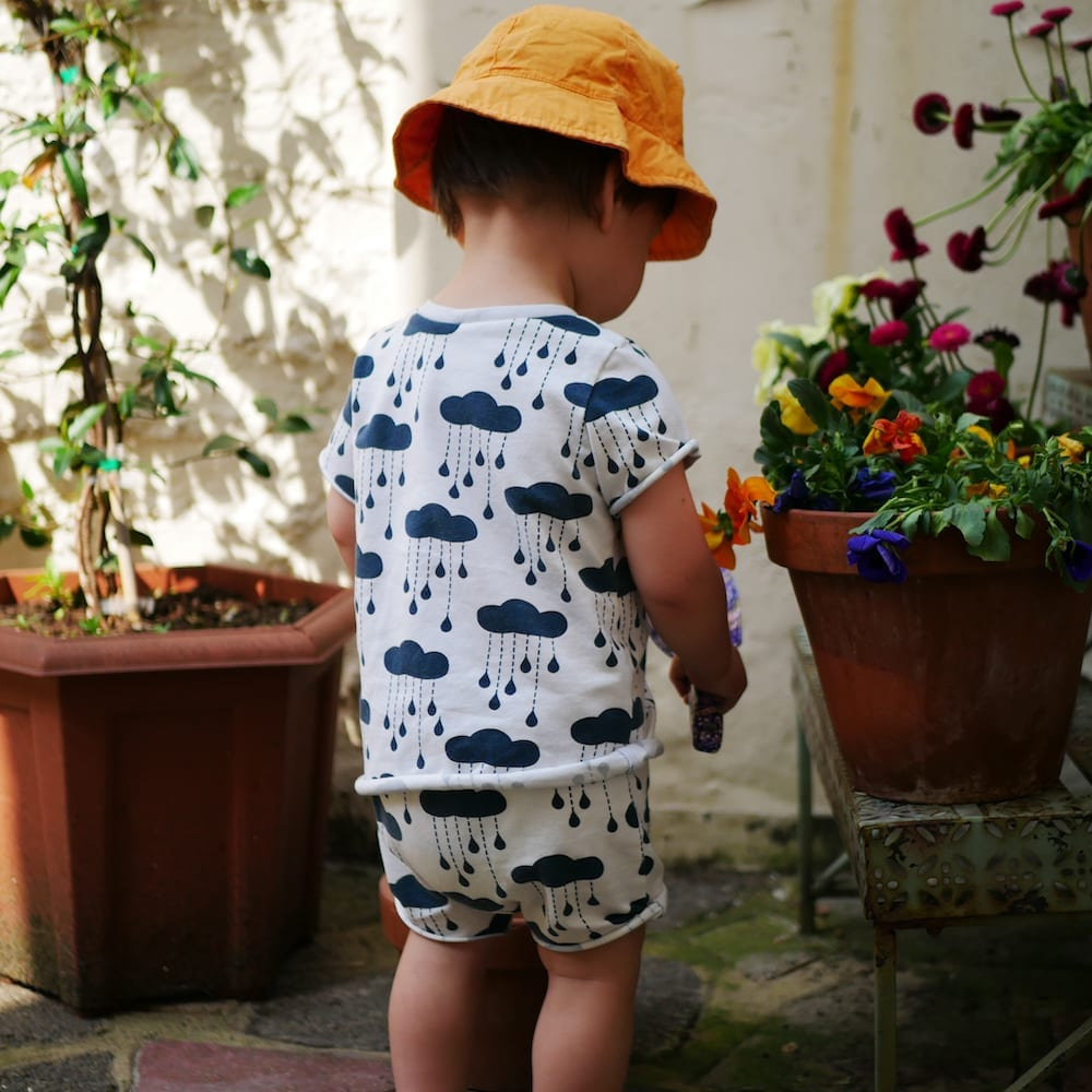 A toddler stands in the garden wearing an outfit made from organic cotton jersey with rain clouds printed on it.