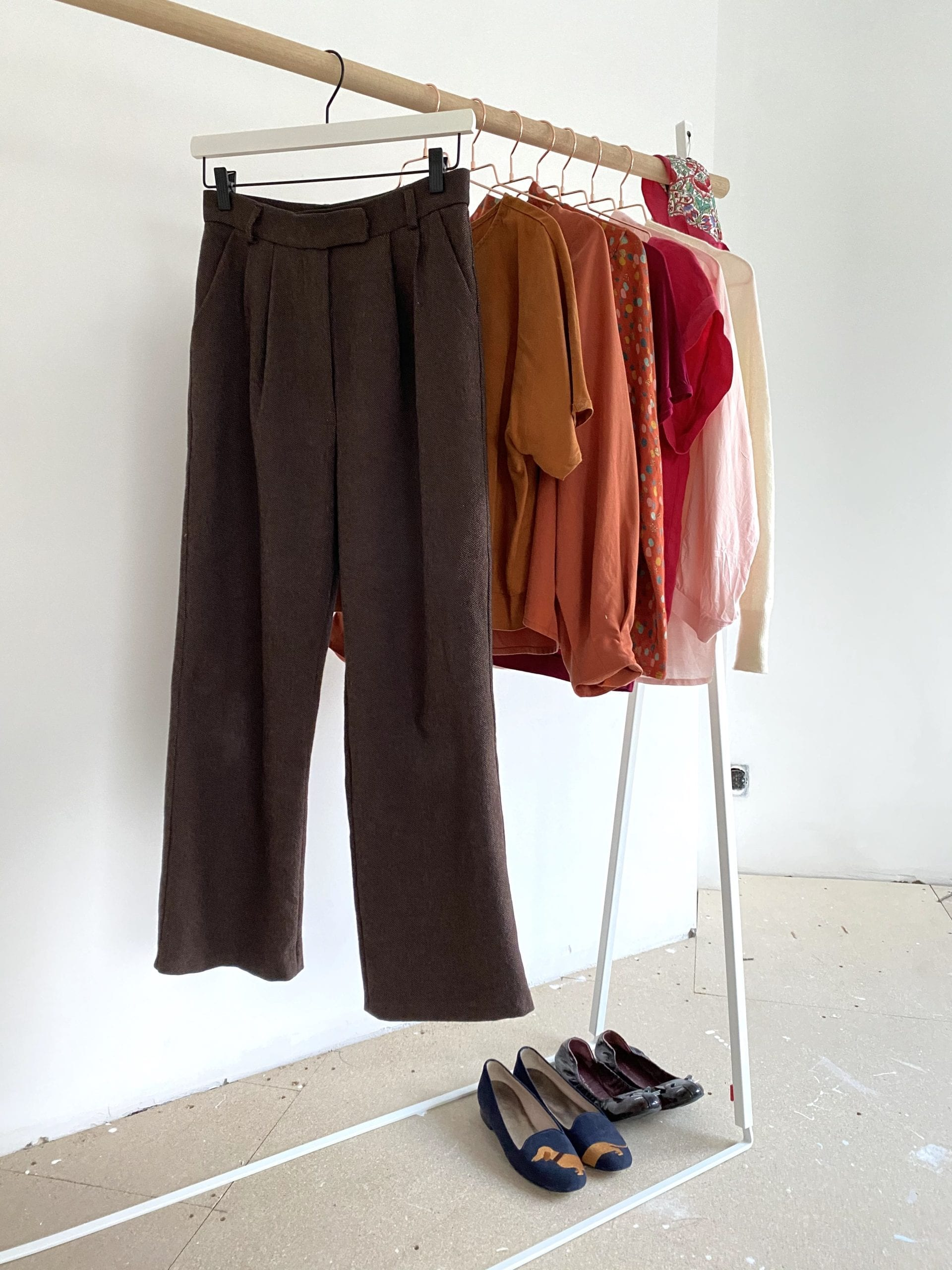 Brown trousers on a rack with a selection of colourful clothes, and two pairs of shoes