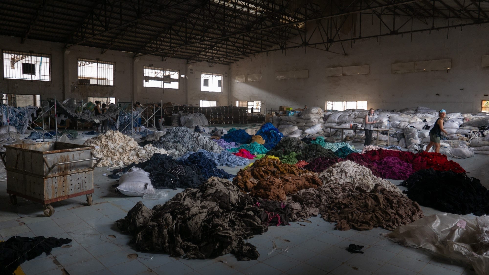 """Image from Unsplash. The image owner captioned this """"Sorting through hundreds of tons of clothing in an abandoned factory for a social mission called Clothing the Loop"""" (Cambodia)"""