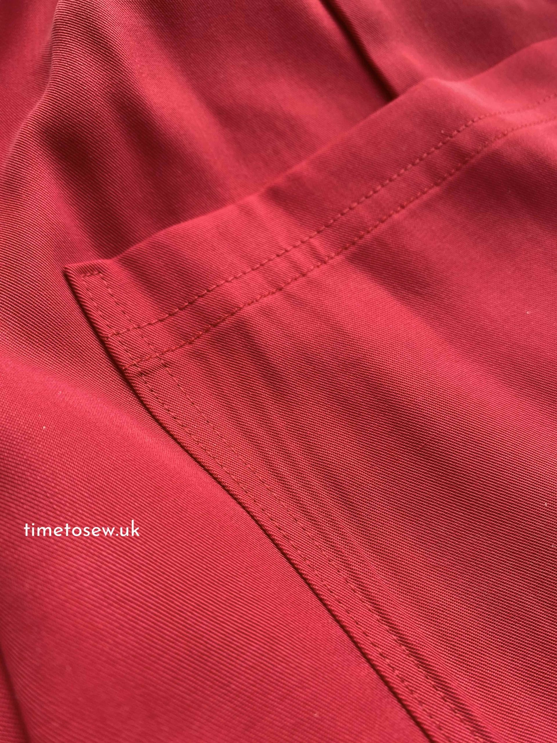 Sewing details, double topstitching on the pocket of a red garment