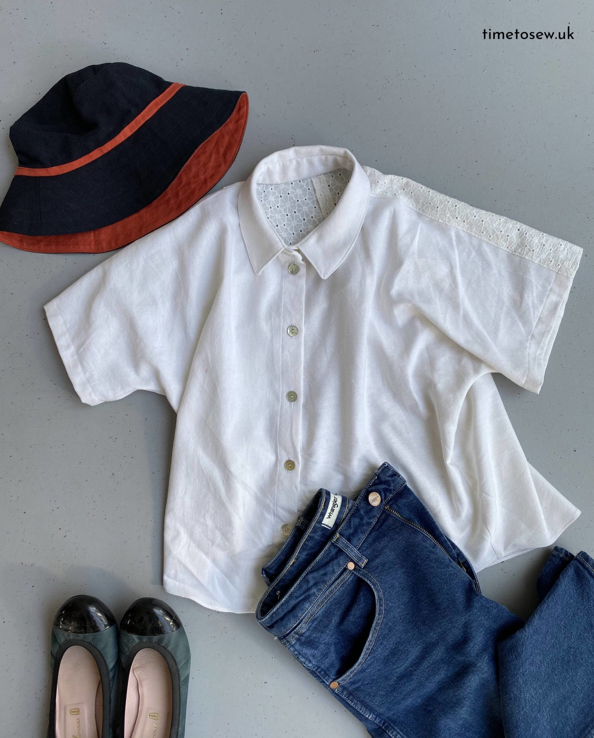 Flatlay of Fibre Mood Aila, a white button down shirt, with a sunhat, ballet flats and jeans.