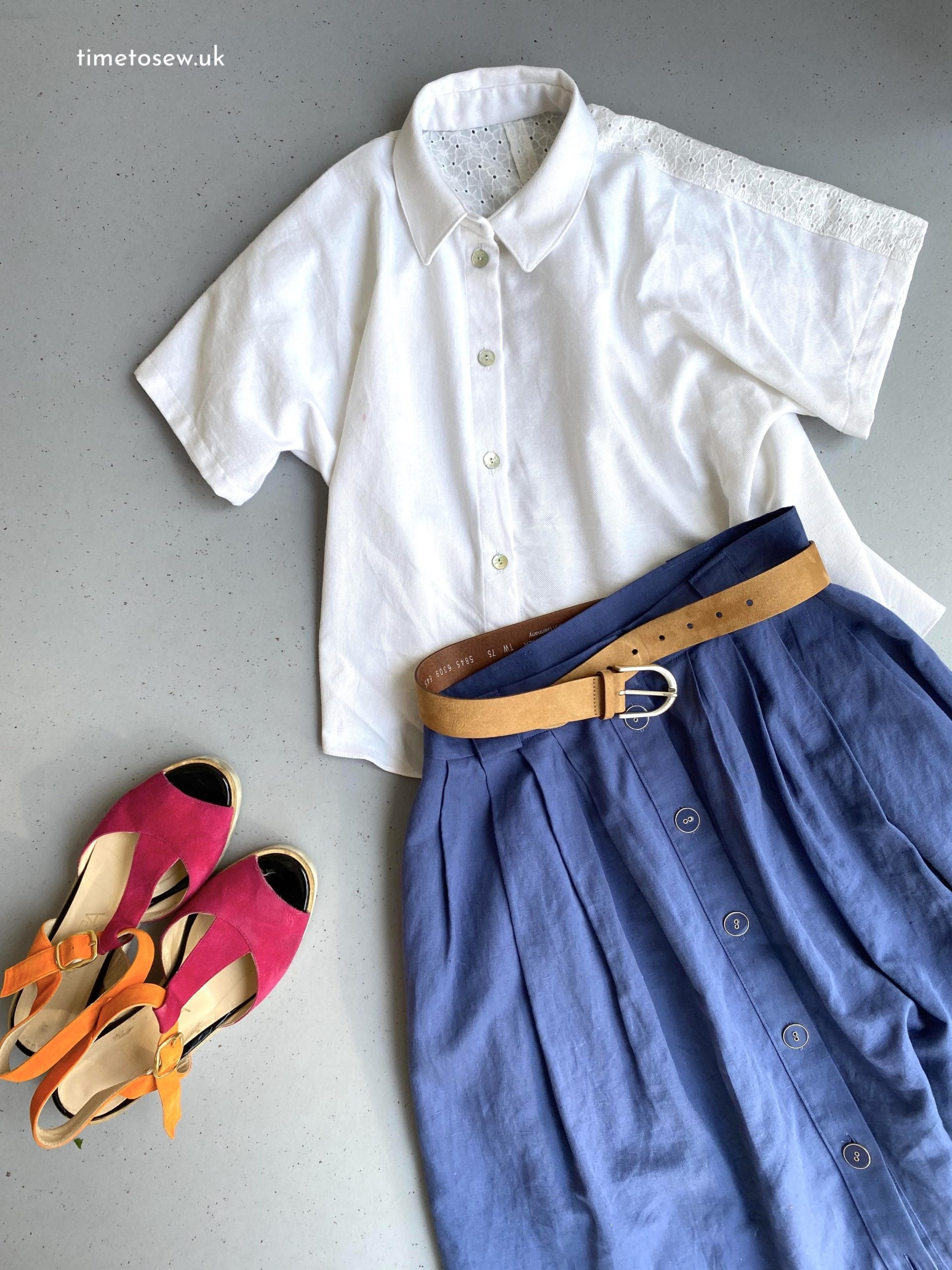 Flatlay of Fibre Mood Aila, a white button down shirt, with a blue skirt, brown belt, and pink and orange sandals